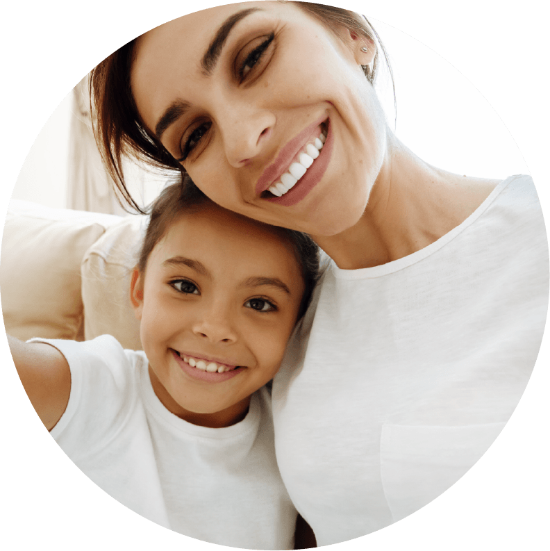A mother and child with white shirts smiling together.