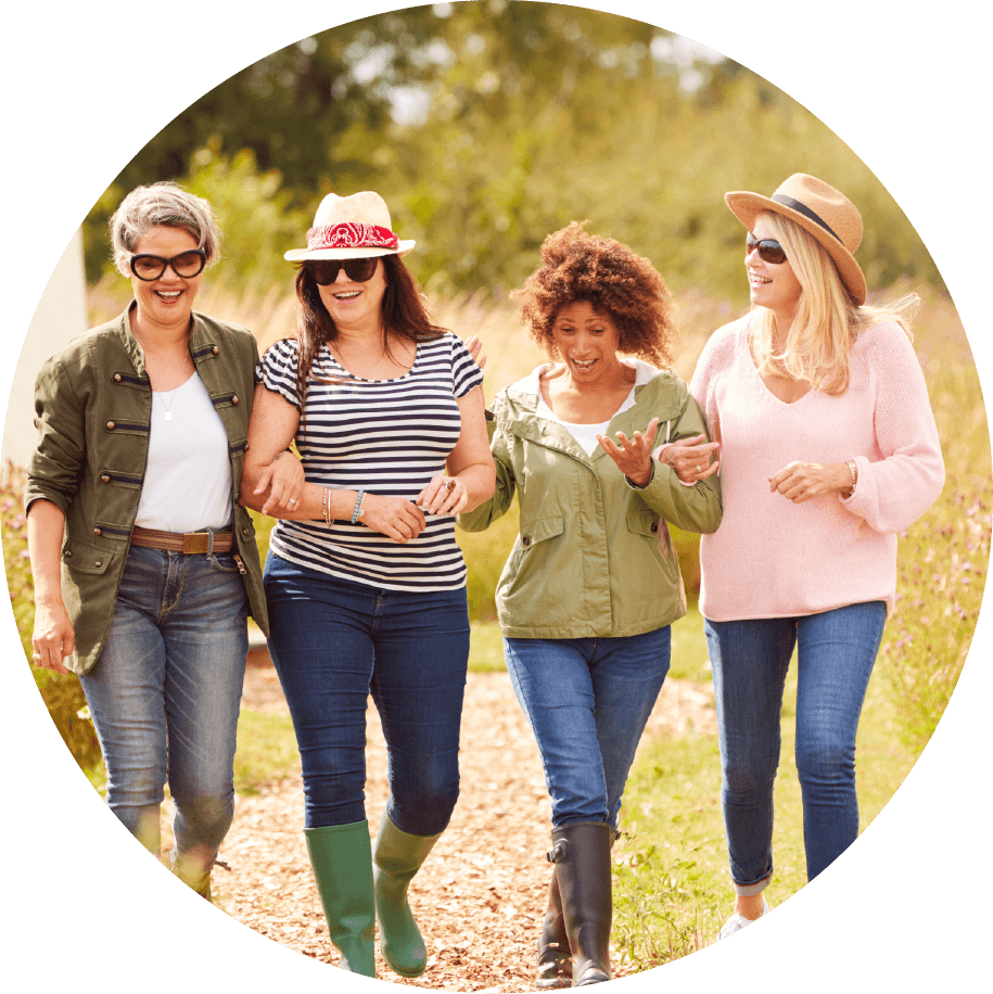 A group of fashionable women walking together down a path.