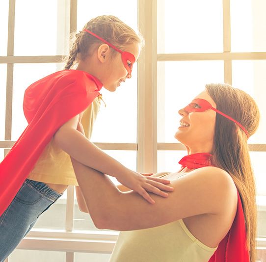 mother and her little daughter dressed like superheroes are looking at each other and smiling.